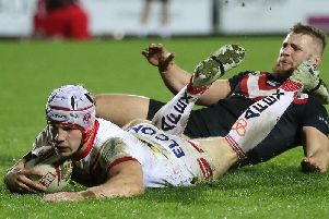 Saints' Theo Fages goes over for a try past London Broncos' Matthew Davies