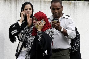 People wait outside a mosque in Christchurch waiting for news about loved ones caught up in two mass killings.