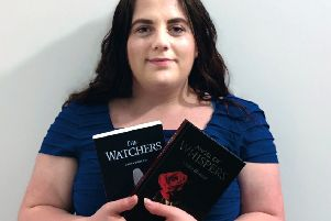 Sutton author Laura Birzulis with the first two books of her Watcher trilogy.