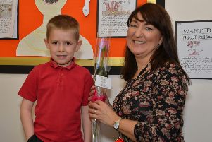 Guardian Rose presentation to Redlands Primary School teaching assistant Liane Tuke from pupil Ethan Myers, six