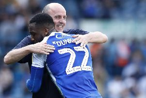 Paul Cook celebrates with Chey Dunkley after Wigans win at Leeds on Good Friday