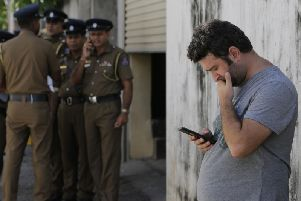 A foreigner checks his mobile phone while waiting outside a mortuary of a hospital, a day after series of blasts, in Colombo, Sri Lanka. PIC: AP Photo/Eranga Jayawardena