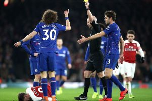 Referee Anthony Taylor brandishes a yellow card during a clash between Chelsea and Arsenal.