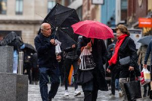 Office workers and shoppers sheltering from the rain whilst in the centre of Leeds.
