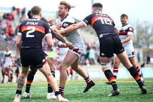 Anthony Mullally of Toronto Wolfpack is tackled by Ethan Ryan and James Green of Bradford Bulls.