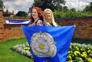 Rebecca Hoggarth-Hall (left) and Angela Kay from the Yorkshire Countrywomen Association wrapped in the Yorkshire flag at their gathering in the Walled Gardens at Temple Newsam, Leeds on Yorkshire Day. Picture by Gary Longbottom.