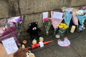 Floral tributes are left on a bridge in Radcliffe, Greater Manchester