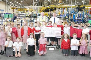 James Woodhouse and pupils at Clayton-le-Woods Primary School hand a cheque to Leyland Trucks Helping Hand
