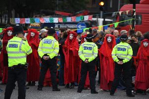 Members of The Red Brigade of The Invisible Circus gesture to police by Lambeth Bridge on October 7, 2019 in London, England. Climate change activists are gathering to block access to various government departments as they start a two week protest in central London (Photo by Chris J Ratcliffe/Getty Images)
