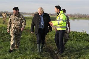 Prime Minister Boris Johnson walks with Lt Col Tom Robinson from the Light Dragoons and Oliver Harmar, Yorkshire Area Director of the Environment Agency, during a visit to Stainforth, Doncaster, to see the recent flooding. Pic: PA