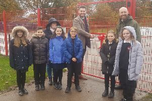 Hucknall councillor Phil Rostance cuts the ribbon to open the gates to the new multi-use games area, alongside head teacher Ed Seeley and children of the school.