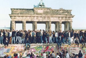 November 1989, East and West Germans stand on the Berlin Wall.