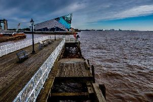 A lone angler braves the cold easterly winds of Yorkshire coast whilst fishing from an old wooden pier into the River Humber whilst one of the UK's most spectacular aquariums The Deep proudly juts out from the dockside over looking the estuary. Picture by James Hardisty.