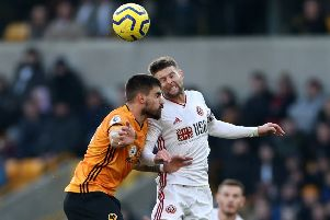 Oliver Norwood: Sheffield United midfielder, right, challenges Wolves Ruben Neves. (Picture: PA)