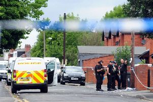Police at the scene of Christopher Lewis's murder in Chapeltown.