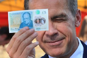 Bank of England Governor Mark Carney holds a new plastic �5 note