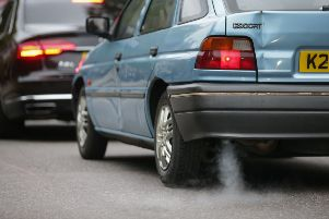A car emits fumes from its exhaust as it waits in traffic in central London.  Photo: Daniel Leal-Olivas/AFP/Getty Images)