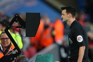 Andy Madley consults the monitor before downgrading the red card he showed Crystal Palace's Joel Ward