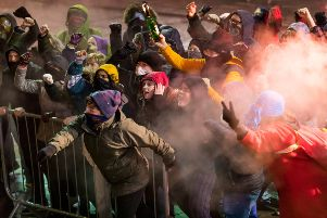 Community actors participate in the riot scene on the steps of Leeds Town Hall for Slung Low's The Good Book. Picture: Chris Thornton