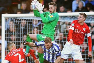 Reds keeper Brad Collins collects under the challenge of Owls' Tom Lees.