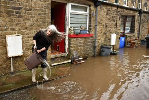 A resident of Mytholmroyd empties water out of their flooded home.