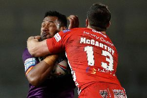 Huddersfield Giants' Ukuma Ta'ai is tackled by Salford Red Devils' Tyrone McCarthy..
