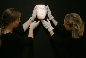 Members of staff at Bonhams in London look at a Mask sculpture by Henry Moore, before it is offered at auction. The work is one of 12 known, small carvings by Moore titled Mask, and is the only one carved from alabaster. It is estimated to fetch �1m to �1.5m.