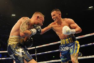 TAKE THAT: Josh Warrington on the attack as he retained his IBF world featherweight title against Carl Frampton in Manchester on Saturday nigvht. Picture: Steve Riding.