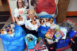 DONATIONS: Prison officer Vicky Morrell hands over gifts to Lauren Procter at the Mission Christmas HQ at the Store Room in Millshaw.