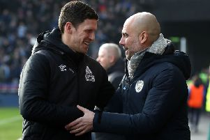 Huddersfield Town caretaker manager Mark Hudson, left, and Manchester City boss Pep Guardiola shake hands prior to kick off at the John Smith's Stadium (Picture: Martin Rickett/PA Wire).