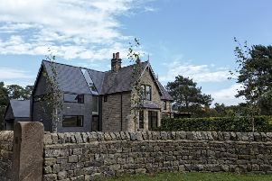 The double-height, blue-black brick extension. is submissive to the original house. The dry stone wall by Ashley Walker encloses the property