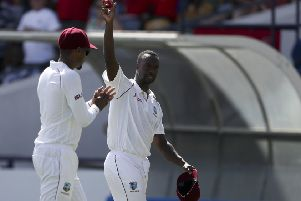 West Indies' Kemar Roach shows the ball after taking five wicket during day two of the first cricket Test match against England at the Kensington Oval in Bridgetown. (AP Photo/Ricardo Mazalan)