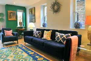 The sitting room in white and billiard room green. The sofa and chair are from Bo Concept and the rug is from York's Handmade Rug Company.