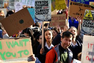 Young demonstrators hold placards as they attend a climate change protest
