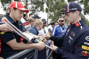 Red Bull driver Max Verstappen of the Netherlands, right, signs autographs as he arrives at the track of the Australian Grand Prix in Melbourne, Australia. (AP Photo/Rick Rycroft)