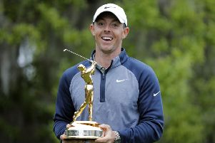 Rory McIlroy poses with the trophy after winning The Players Championship golf tournament.