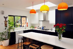 The kitchen area with vintage lights from Etsy and a collection of vintage stools surrounding the island.