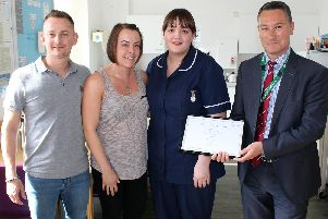 Midwife Sister Rebecca White (centre) receives the Employee of the Month Award from Chief Executive Kevin McGee, with Simon and Carla Thompson to her left.