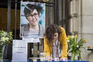 People signing a book of condolence after a vigil at Belfast City Hall in memory of murdered journalist Lyra McKee.