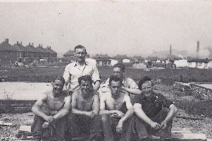 Builders on the emerging Athersley estate take a break during the 1950s, with 'prefab' homes in the background