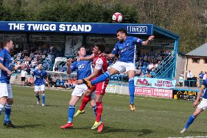 Matlock's Dwayne Wiley rises to head clear another Buxton attack.
