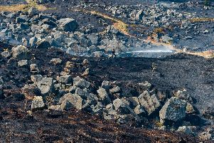 Firefighters continue to damp down following a moorland fire on Ilkley Moor which has affected a large area of the moorland.