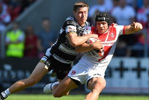 St Helens' Jonny Lomax  is tackled by Hull FC's Jamie Shaul.