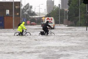 People cycling through water on Cleveland Street in Hull, after the floods of 2007, which brought devastation to the city and Sheffield and left three people dead