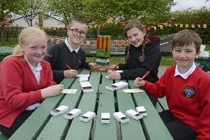 Newsham Primary School pupils Eve, Ryan, Evie and Reid writing new memories for this year's matchboxes and with the trophy they won in the same event last year.  Picture by Jane Coltman.