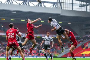 Huddersfield's Jake Wardle, left, and Hull FC's Jake Connor battle for a kick at Anfield. (PIC: Alex Whitehead/SWpix)