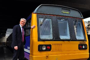 Rail Minister Andrew Jones at Leeds station with a Pacer train.