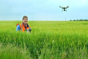 Richard Dee a drone operator flying  his drone over a field of winter barley near to Hornsea.
