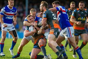 James Clare is tackled by the Wakefield Trinity defence - but the Castleford Tigers winger escaped long enough later to scorer a hat-trick of tries. (PHOTO: JAMES HEATON)