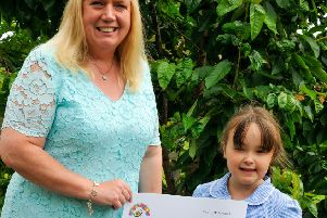 Tabitha receiving a cheque from the school's head teacher, Kim Tucker. (PHOTO BY: Louise Brimble)